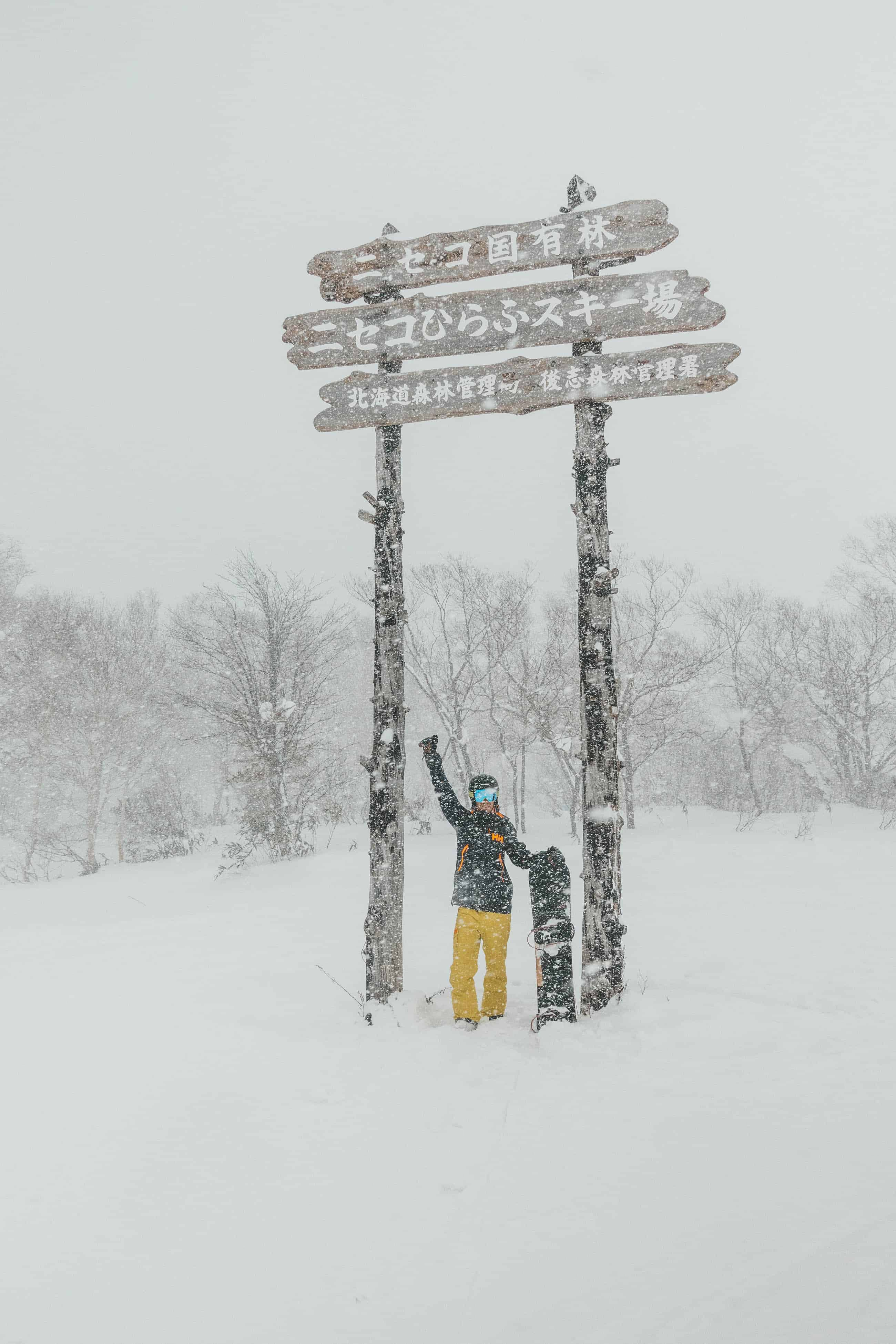Cameron Standing in Niseko Hanazono Sign in Japan with Snowboard