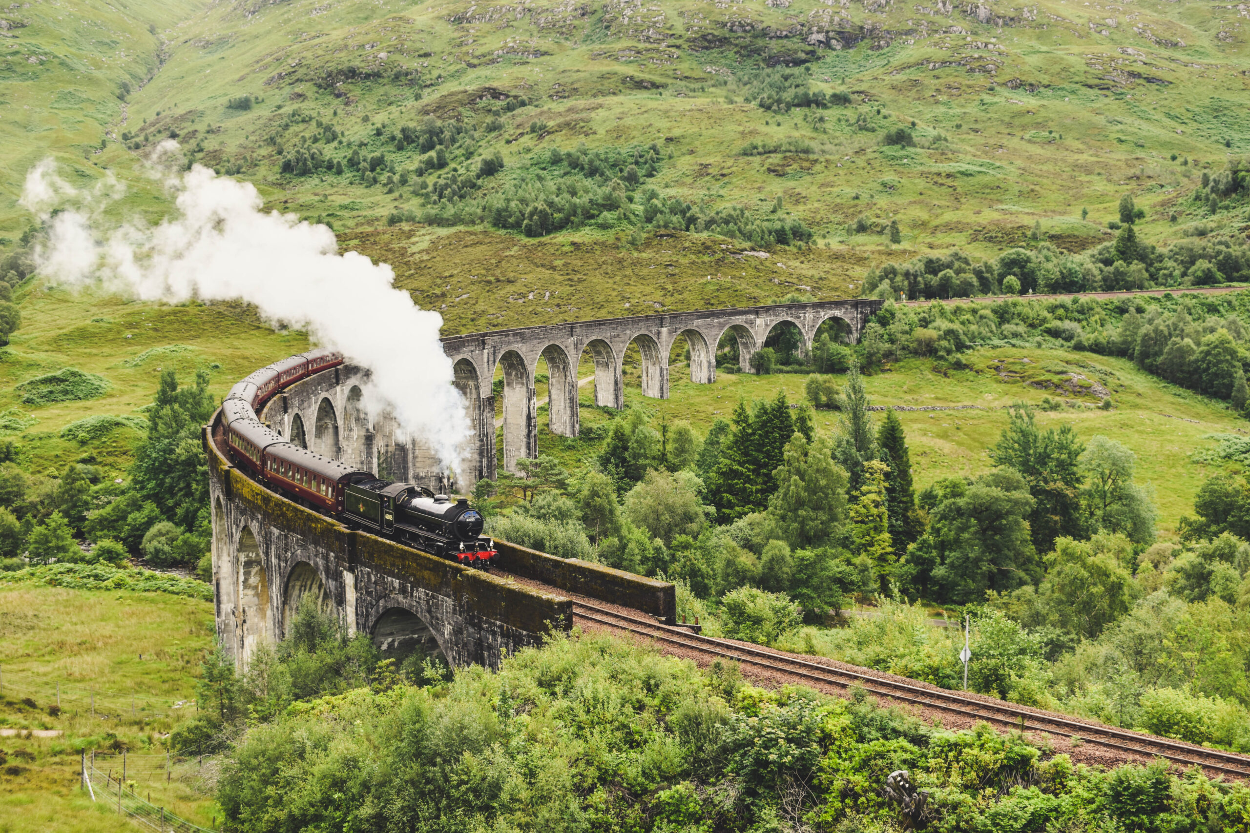 Jacobite train driving across Glenfinnan Viaduct