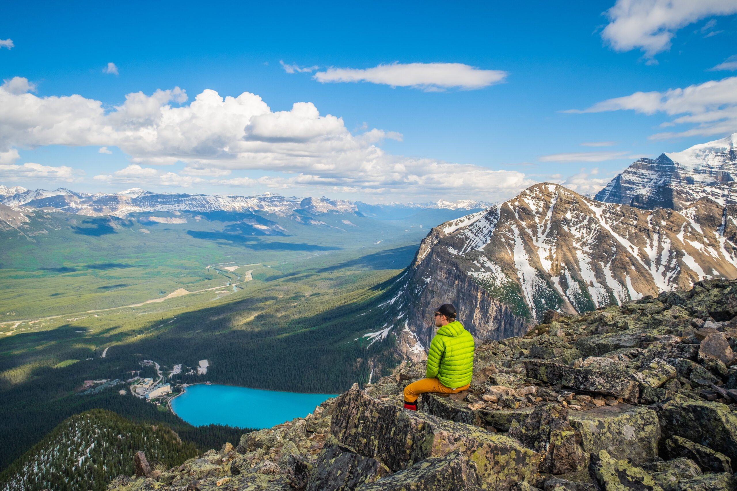 Cameron Sits Above Lake Louise In A Down Jacket