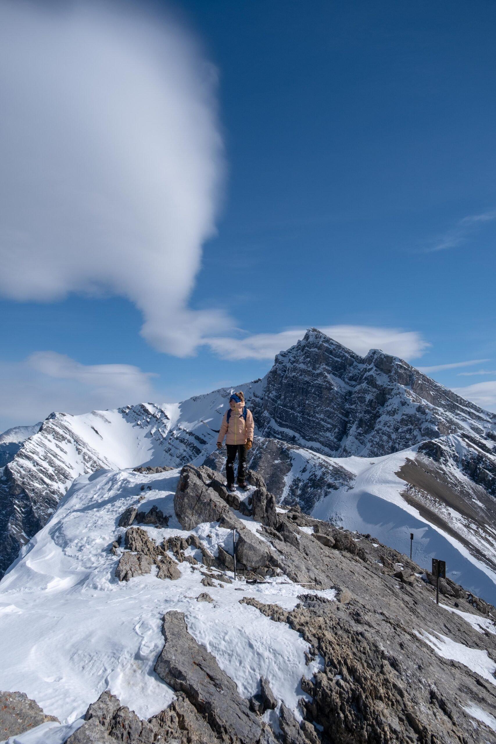 Natasha on the summit of Ha Ling Peak with multiple layers