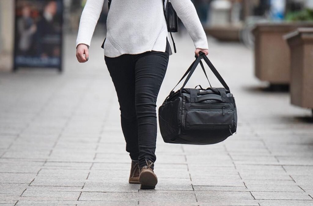 Woman Carrying Nomatic Travel Bag