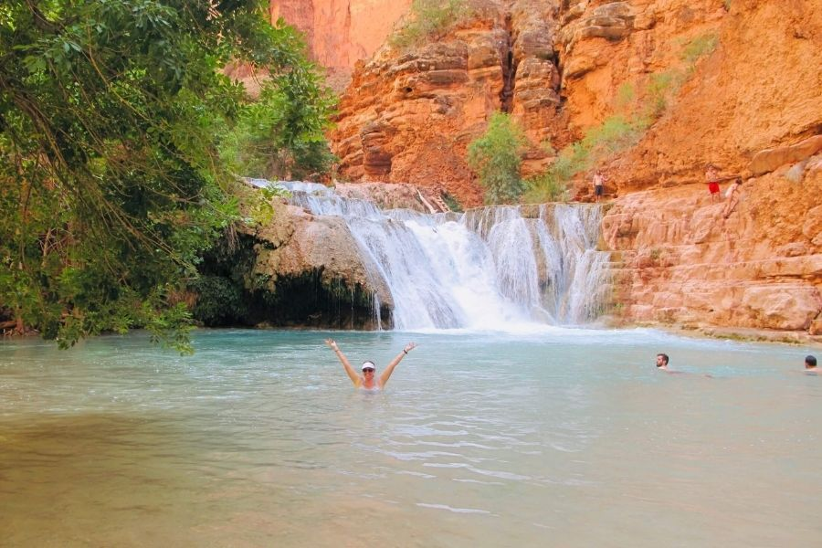 beaver falls, havasupai, woman with her arms raised in the waterfall pool