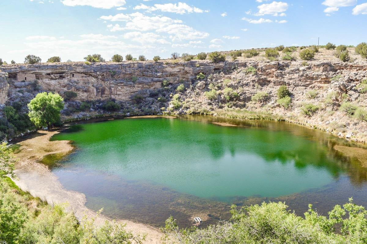 Sinkhole at Montezuma Well National Monument with cliff dwellings in the cliff side