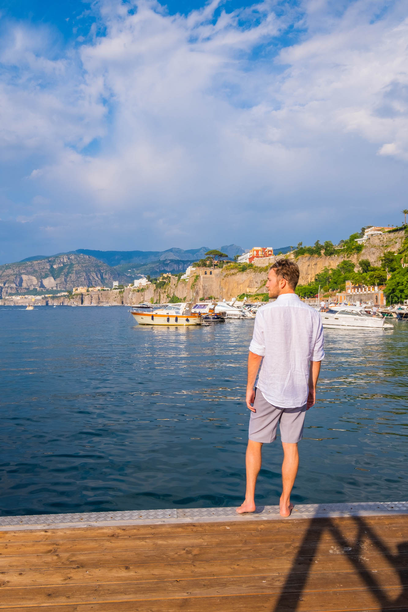 Cameron on the dock in Sorrento in linen shirt and board shorts
