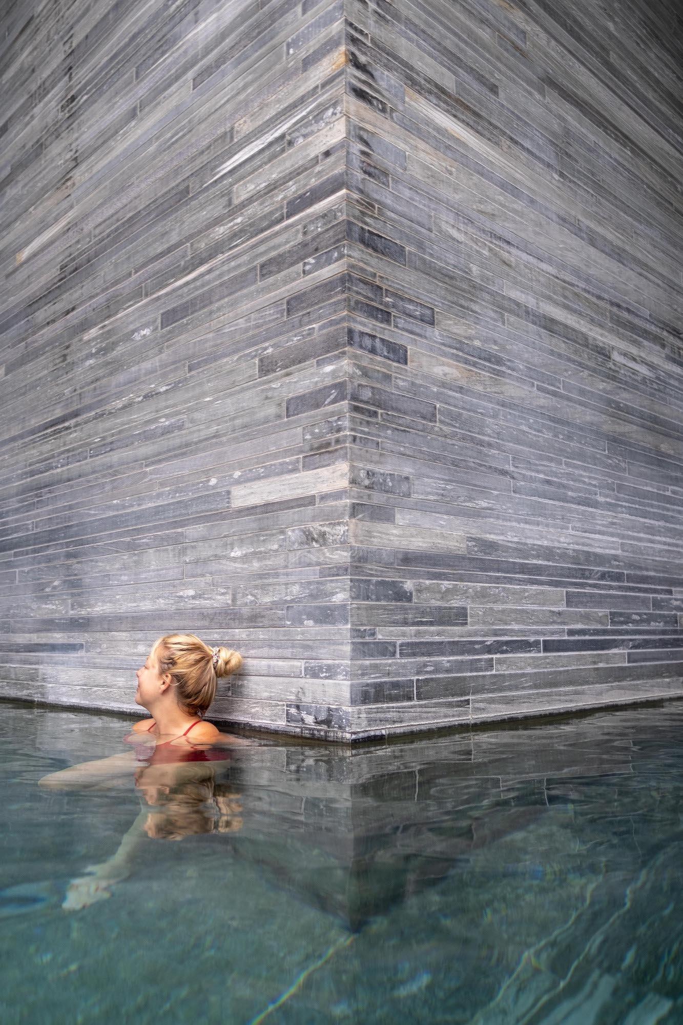 Tasaha soaking along quartzite wall in Therme Vals